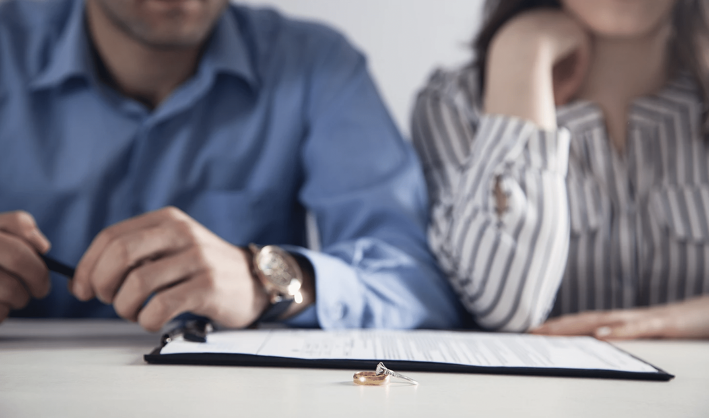 Couple signing divorce papers with rings on the table