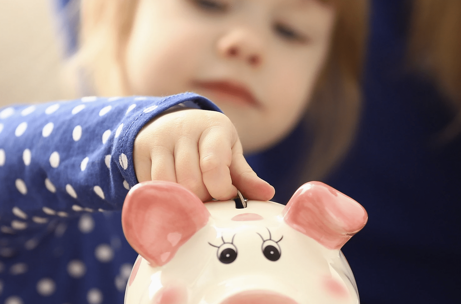 Baby putting money in piggy bank