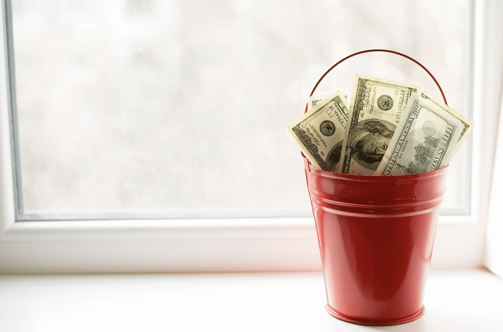Red bucket filled with $100 bills