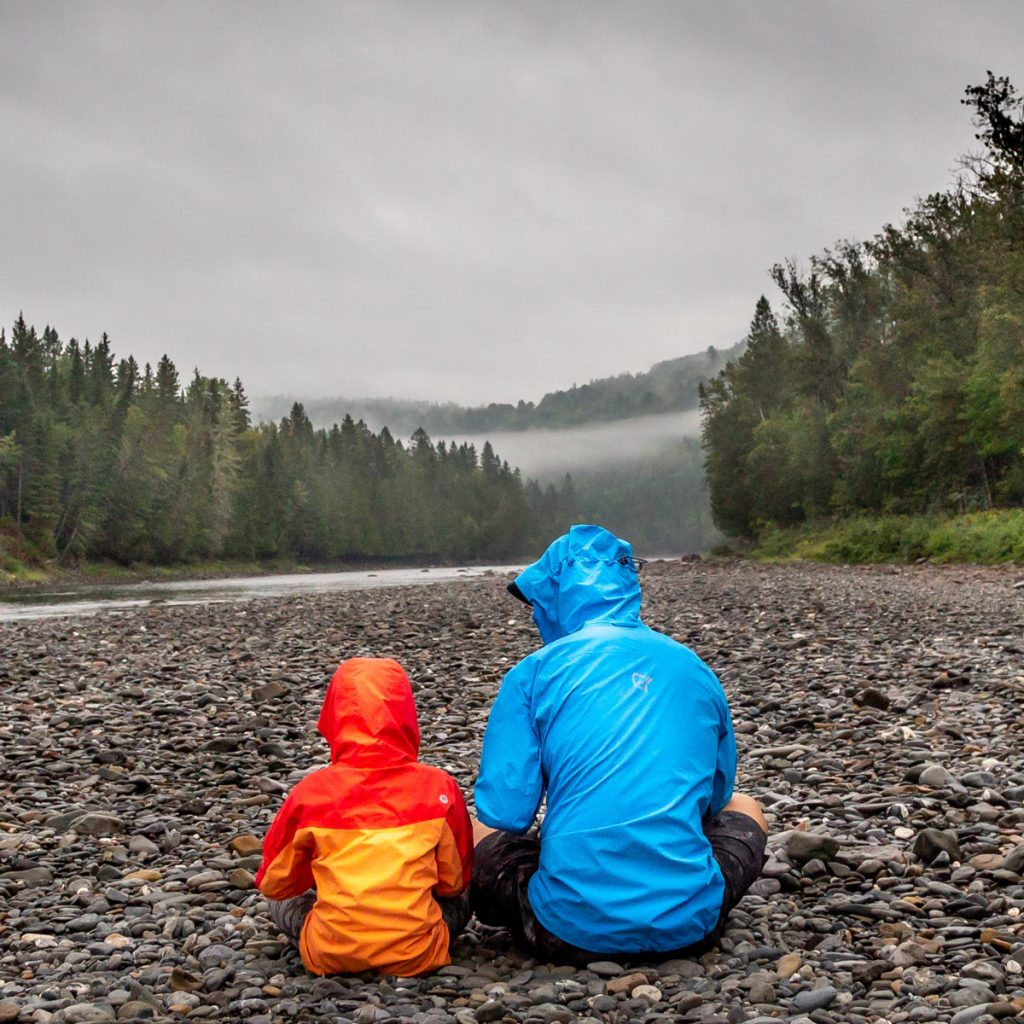 Dad and son sitting by river in forest